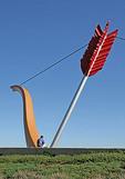 Man sitting at base Cupid's Span sculpture Embarcadero, San Francisco California