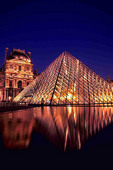 The Louvre Museum glass pyramid at night in Paris France
