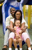 Black African American couple with daughter on slide in park on family day outdoors