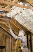 Ecology saving energy in home by spraying insulation into ceiling to save money on electricity