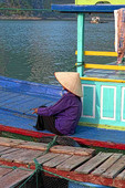 Picturesque scene old woman in purple in fishing village Halong Bay Ha Long relax Vietnam