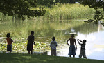 Black kids playing at a pond in the summer
