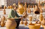 Woman tourist shopping for pottery clay pots in shop in the beautiful Algarve village of Vila de Bispo Portugal