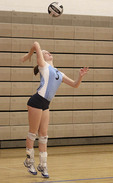 Girl serving ball in high school volleyball game