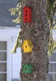 Three birdhouses on a pine tree