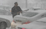 Man cleaning car window in winter storm