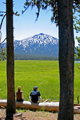 Couple sitting at  Sparks Lake near Mt. Bachelor on Cascade Lakes National Scenic Byway Oregon
