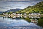 Beautiful  photo of small village of Dornie with refections and boat in Western Highlands Scotlands