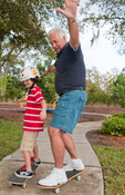 Young boy and grandfather skate boarding
