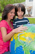 Woman with young boy looking at large globe