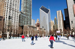 Skaters circle the ice rink in Millenium Park along Michigan Avenue on a sunny winter morning in Chicago.