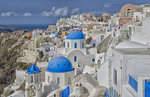 White buildings with steep slope with blue dome churches on mountain in Fira in Santorini Greece in Greek Islands