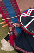 Close up from above of woman in traditiuonal dress as weaving rug near Cusco Cuzco Peru
