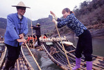 Man and a woman Guiding rafts down stream Fujian Province, China Wuyi Mountain.