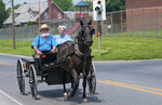 Amish couple in old fashioned horse carriage on street in  Intercourse Pennsylvania in Lancaster area of Amish country