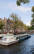 The wonderful canals and buildings beside the river and the tourist boats riding on the water in Amsterdam Holland Netherlands on a  sunny day