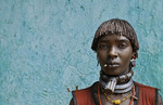 Dimeka Ethiopia Africa village Lower Omo Valley portrait of attractive Hamar woman with necklace showing First Wife against green wall