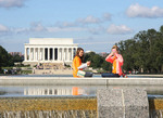 Young tourist at World War II Memorial with Linclon Monument in background