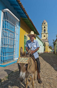 Trinidad Cuba old man on donkey selling rides and photos in old colonial town with cobble stones and church