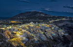 City of Fira Santorini Greece at night from mountains with sky and lights