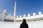 The beautiful interior of the white Sheikh Zayed Grand Mosque in Abu Dhabi in the UAE the worlds 8th largest Muslim mosque in the world with Muslim tourist in United Arab Emirates