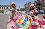 Havana Cuba local women with flowers at Capital in pink Classic Ford auto and hats smiling for tourists