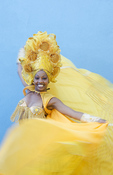 Trinidad Cuba dancer in show costume gold against blue wall and colorful  head dress and smile