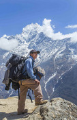 Nepal. Mountain Trekking guide poses with his bags and the Himalayan mountains  in the distance.