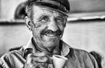 Local man portrait with Greek coffee with Greek hat at restuarant in white in Mykonos in Greek Islands in Greece Europe