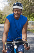 Black african american man in 40s dressed in sports wear on bike exercising in park with no business stress