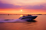 Couples running motor boat with wake and excitement as it moves thru water with speed at sunset on colorful sky
