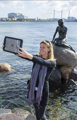 Copenhagen Denmark Little Mermaid monument Den Lille Havfrue with tourist woman taking Ipad photo