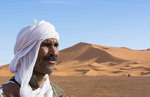 Morocco Sahara Desert sand dunes in Las Palmeras area with portrait of local man in turbin and peaks and sand