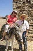 Greece Paros Cyclades old local man with donkey near Lefkes in mountains at his farm home with woman tourist on donkey