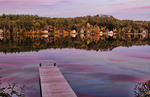 Norway Maine beautiful fall scene of pier on Lake Pennasseewassee with summer homes and fall colors in leaf peeping October with reflections in the water in Northern New England
