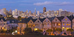 San Francisco California Painted Ladies Victorian homes and city in background at Alamo Square at Hayes Street and Steiner Street at sunset