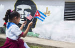 Las Terrazas Cuba elementary school student with American and Cuban flag and Che mural on wall