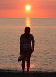 Woman looking out over Lake Erie at sunset