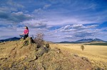 Woman meditating amid vast Western landscape at Government Prairie with San Francisco Peaks in background, Kaibab National Forest, Arizona, AGPix_0417