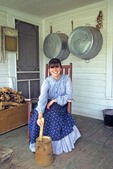 Young woman demonstrates soap making while sitting on porch of 1900  era farm house at Living History Farms, Des Moines, Iowa, AGPix_0502