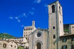 Gubbio, an ancient Umbrian hill town with facade of San Giovanni Battista and the Palazzo Dei Consoli on hill in back at Gubbio, Umbria, Italy, AGPix_0510