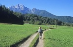 Hiker on rural roadway near village of Kranjska Gora in the Julian Alps, Slovenia, AGPix_0552