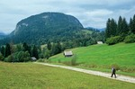 Hiker on rural road, with Rudnica Hill in distance, in the Julian Alps Region, near Bohinjska, Slovenia, AGPix_0558