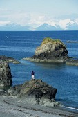 Hiker on rocky shore of Shuyak Island State Park with view across Shelikof Strait toward Mount Douglas, north of Kodiak Island, Alaska, AGPix_0676