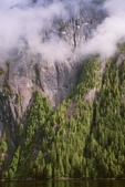 Sheer rock cliffs with clouds and forest at Rudyerd Bay in Misty Fiords National Monument in Tongass National Forest east of Ketchikan, Alaska, AGPix_0697