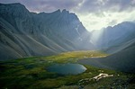 Sunlight spills from behind clouds into unnamed valley amid rugged peaks of the Endicott Mountains in the Brooks Range at Gates of Arctic National Park, Alaska, AGPix_0735    