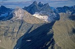 Bush airplane flying amid the Arrigetch Peaks in the Brooks Range at Gates of the Arctic National Park, Alaska, aerial view, AGPix_0738