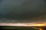 Sunset behind  dark storm clouds of a severe thunderstorm along wet country road on the Great Plains near Woodruff, Kansas, AGPix_0905