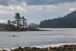Sea kayaker in waters off Ross Island in Gwaii Haanas National Park Reserve, in the Queen Charlotte Islands of British Columbia, Canada, AGPix_0915