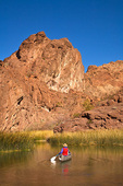 Canoeing along shoreline of rugged desert mountains and reedy vegetation on a back bay of Colorado River in Topock Gorge in Havasu National Wildlife Refuge, near Lake Havasu City, Arizona, AGPix_1049